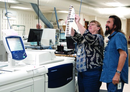 Renee Hahn and Roman Aragon check a proof printed on the Xerox DocuColor 700.